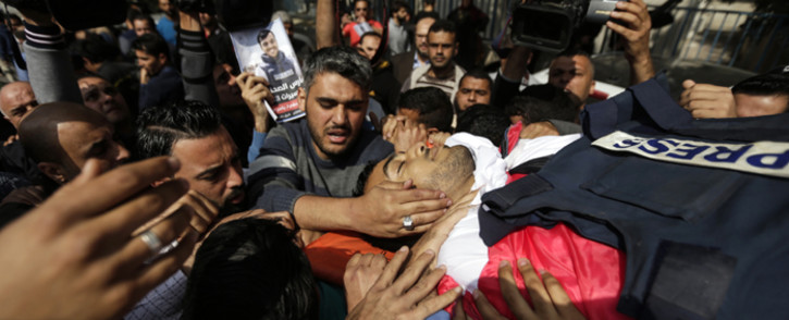 Mourners and journalists carry the body of Palestinian journalist Yasser Murtaja, during his funeral in Gaza City on 7 April 2018. Picture: AFP