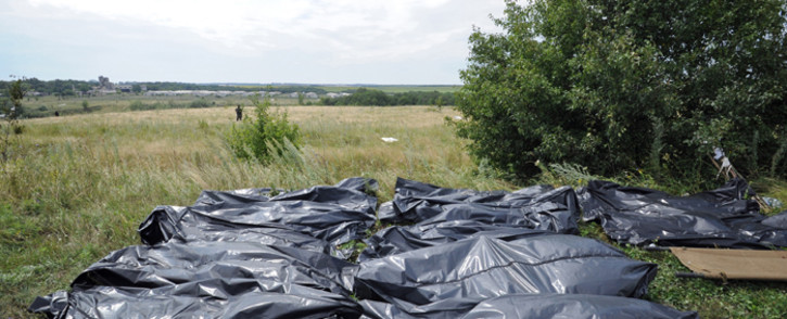 Bodies of victims wrapped in bags wait to be collected at the site of the crash of a Malaysia Airlines plane carrying 298 people from Amsterdam to Kuala Lumpur in Grabove, in rebel-held east Ukraine, on 19 July, 2014.
