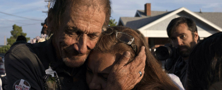 Antonio Basco, husband of El Paso Walmart shooting victim Margie Reckard, hugs and attendee during his wife's visitiation service outside La Paz Faith Center in El Paso, Texas on 16 August 2019. Picture: AFP