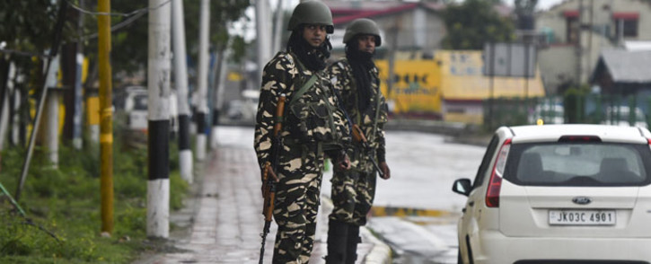 Security personnel stand guard near a closed school in Srinagar on 19 August 2019. Picture: AFP