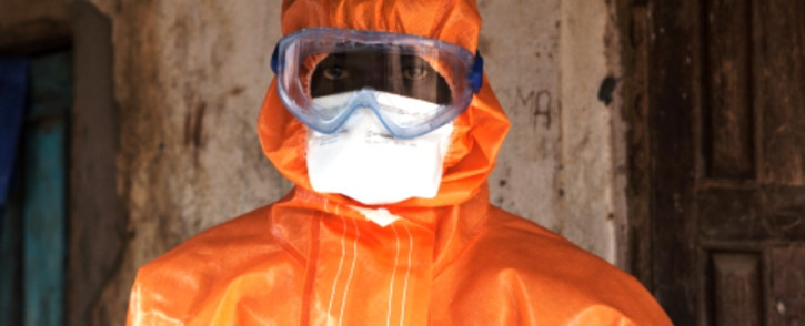 A volunteer in protective suit looks on after spraying disinfectant outside a home in Waterloo, some 30 kilometres southeast of Freetown, on 7 October 2014. Picture: AFP.