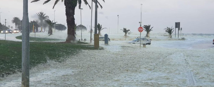 Vehicles drive through foam and seawater that has crashed over the promenade and onto the road during a storm near Beach Road in Sea Point on 13 July 2020. Picture: Supplied