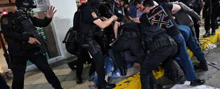 Policemen subdue a hostage-taker (obscured) after he surrendered outside a mall in Manila on March 2, 2020. Picture: AFP