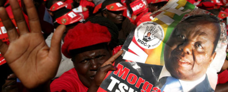 Supporters of the Movement for Democratic Change presidential candidate Morgan Tsvangirai hold his portrait as they attend the final campaign rally 'Cross Over' on 29 July 2013 at the Freedom Square in Harare ahead of the general elections held on 31 July 2013. Picture: AFP.