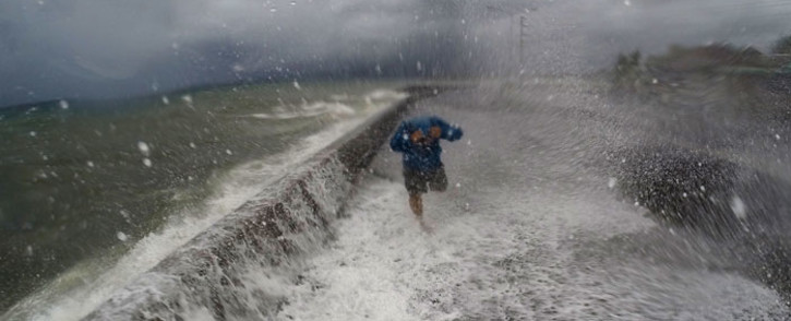 FILE:  resident walks past big waves spilling over a wall onto a coastal road in the city of Legaspi in Albay province, south of Manila on December 14, 2015, as typhoon Melor approaches the city. Picture: AFP /Charism Sayat