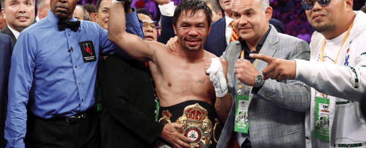 Manny Pacquiao poses with members of his team and referee Kenny Bayless after defeating Keith Thurman by split decision in a WBA welterweight title fight at MGM Grand Garden Arena on 20 July. Picture: AFP.