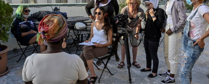 Young refugees and Greek women film during an interview on gender-based violence with Loretta Macauley, from African Women Organization Greece in Athens on 25 May 2021. Picture: LOUISA GOULIAMAKI/AFP