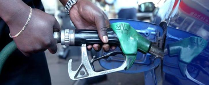 A petrol station attendant fills up a car tank. AFP