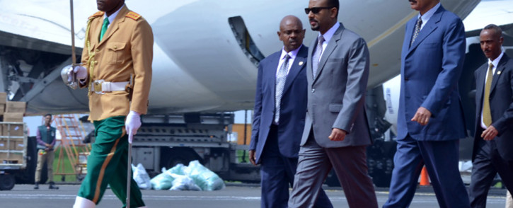 Eritrea's President Isaias Afwerki (2R) is received by Ethiopia's Prime Minister Abiy Ahmed (3R) as he arrives at Bole International airport in Addis Ababa on 14 July 2018. Picture: AFP.