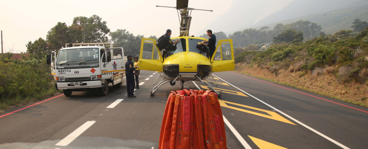 A Working On Fire chopper lands on a stretch of road while fighting the Overstrand fires near Cape Town. Picture: Bertram Malgas/EWN