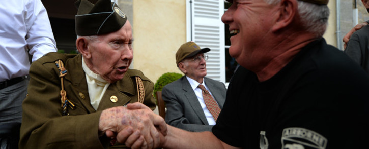 US World War II veteran Joe Riley, 98-years-old, of the 501th Airborn, shakes hands with a WWII enthusiasts, in Sainte-Marie-du-Mont, northwestern France, on June 6, 2019, during celebrations marking the 75th anniversary of the D-Day landings. Picture: AFP