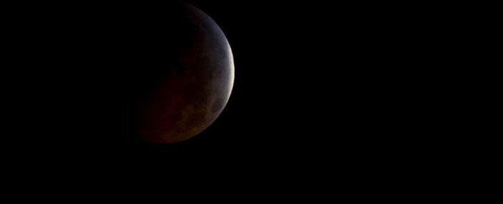 FILE: The moon turned dark before shining orange, brown and crimson in the shadow during the longest lunar eclipse of the 21st century on 27 July. Picture: @NASA/Twitter.