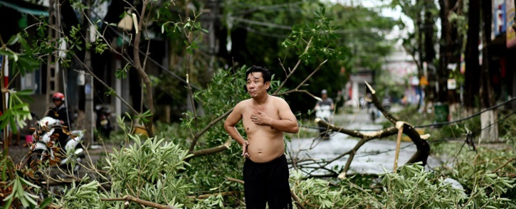 A man reacts while standing amidst uprooted trees in central Vietnam's Quang Ngai province on October 28, 2020, in the aftermath of Typhoon Molave. Picture: AFP