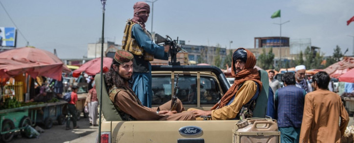 Taliban fighters on a pick-up truck move around a market area, flocked with local Afghan people at the Kote Sangi area of Kabul on August 17, 2021, after Taliban seized control of the capital following the collapse of the Afghan government. Picture: Hoshang Hashimi/AFP