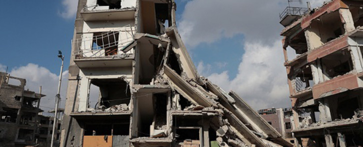 FILE: Syrians walk past a destroyed building in the rebel-held town of Douma, on the eastern outskirts of Damascus. Picture: AFP