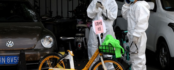 People wearing protective suits use their mobile phones near the Guang'an Sport Center where swab tests for people that live or visited Xinfadi market is taking place in Beijing on 15 June 2020. Picture: AFP