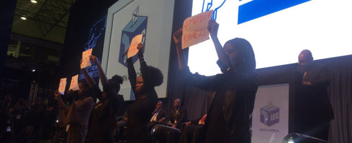 Four female EFF members holding placards in front of the stage as President Jacob Zuma delivers his address at the IEC national results centre in Pretoria. Picture: Masa Kekana/EWN.