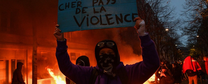 """A protester holds a sign reading """"Sweet France. Dear country of violence"""" in front of a fire during a demonstration in Paris on 5 December, 2020. Picture: AFP."""