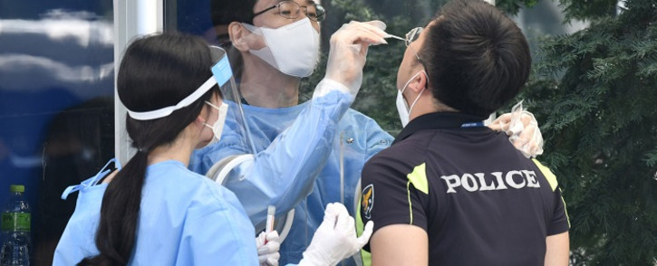 A medical worker in a booth takes test samples for the COVID-19 coronavirus from a South Korean police officer at Seoul Metropolitan Police Agency's maneuver headquarters in Seoul on 19 August 2020. Picture: AFP