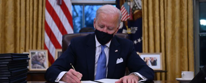 US President Joe Biden sits in the Oval Office as he signs a series of orders at the White House in Washington, DC, after being sworn in at the US Capitol on 20 January 2021. Picture: Jim WATSON/AFP