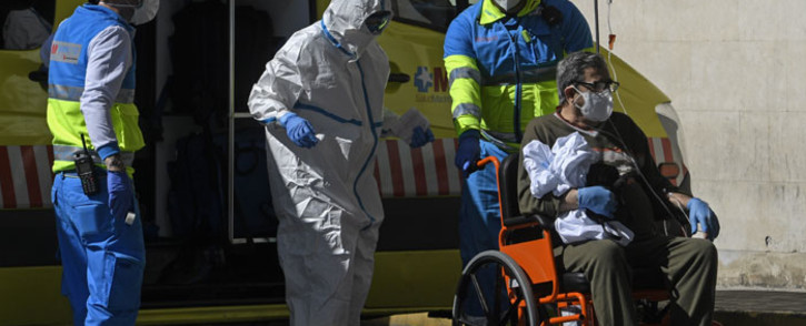FILE: Healthcare workers wearing protective suits push a man on a wheelchair outside the 12 Octubre Hospital in Madrid on 2 April 2020. Picture: AFP