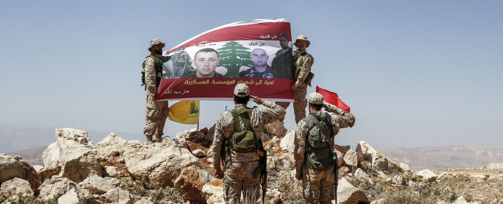 Fighters from the Lebanese Shi'ite Hezbollah movement raise up and salute a banner in a mountainous area around the Lebanese border town of Arsal. Picture: AFP.