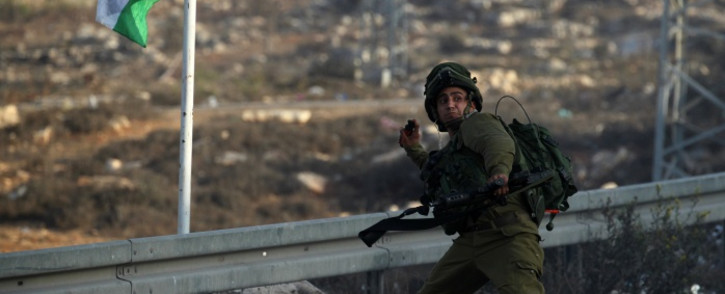 An Israeli soldier hurls a smoke grenade during clashes with Palestinian youth close to the Jewish settlement of Bet El, in the West Bank city of Ramallah on 4 October 2015 after Israel barred Palestinians from Jerusalem's Old City as tensions mounted following attacks on Israelis. Picture: AFP.