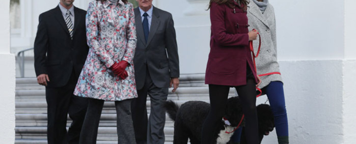 FILE: US first lady Michelle Obama (2nd L), her daughters Sasha Obama (R) and Malia Obama and their family dogs, Bo and Sonny and tree growers Chris Botek (L) and Francis Botek of Lehighton, PA, walk out of the White House before receiving the White House Christmas Tree on the North Portico 28 November 2014 in Washington, DC. Picture: AFP