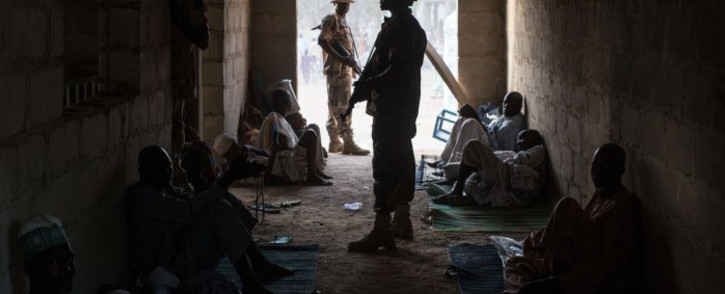 FILE: Nigerian soldiers stand guard next to civilians who fled the fighting in Bama and the surrounding areas at a makeshift camp for displaced people on the outskirts of Maiduguri on 25 March 2015. Picture: AFP.
