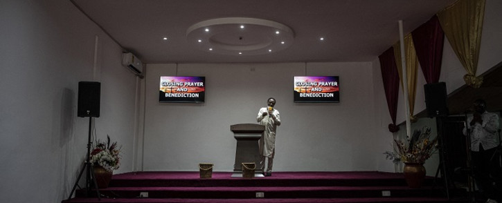 A pastor talks to his congregation in a church in Adenta on April 18, 2021. The number of worshipers assisting the mass has been reduced since the start of the COVID-19 pandemic as only gatherings of 25 people are allowed to attend a service by the government, to prevent the spread of the virus. The pandemic has forced many Christian Ghanaians to change their religious practices, with churches turning to online services and donations, and live streaming funerals. Picture: Cristina Aldehuela / AFP.