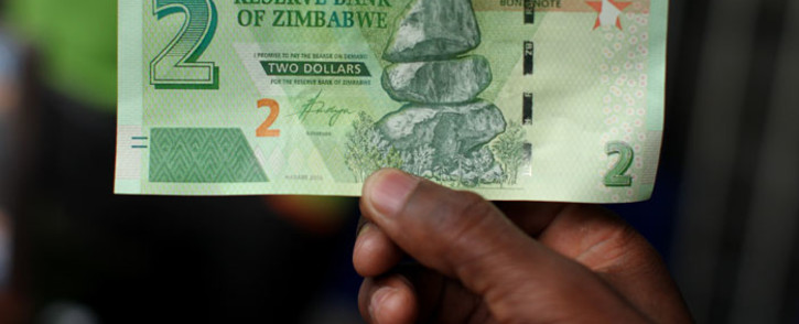 FILE: A man holds a bond note released by the Reserve Bank of Zimbabwe in Harare central business centre on 28 November 2016. Picture: AFP