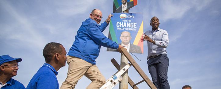 "FILE: ""DA leader Mmusi Maimane (R) and Nelson Mandela Bay mayoral candidate Athol Trollip (L) fix a placard to a lamp post in Bethelsdorp, Port Elizabeth, on 24 June 2016. Picture: Aletta Harrison/EWN."