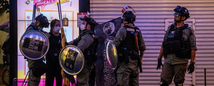FILE: Police detain a woman (2nd L) as pro-democracy protesters gather in the Causeway Bay district of Hong Kong on 12 June 2020. Thousands of Hong Kongers sang a protest anthem and chanted slogans across the city on 12 June as they marked the one-year anniversary of major clashes between police and pro-democracy demonstrators. Picture: AFP.