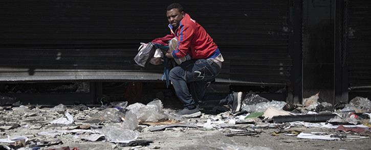 Foreign shop owners gathered what was left of their property after community members looted their stores in Alexandra township on 3 September 2019. Picture: Sethembiso Zulu/EWN