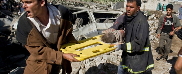 FILE. A screebgrab image shows people carrying an injured child in Yemen after Saudi-led air strikes in an ongoing war between the two countries.