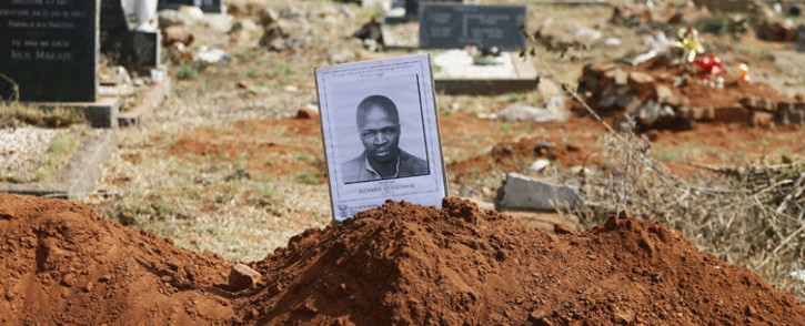 A picture of Richard Motsoahae, one of the four members of the Pan Africanist Congress (PAC) is displayed next to his grave at Mamelodi West Cemetery where his family viewed his mortal remains in Pretoria, South Africa on 15 August, 2018. Picture: AFP.
