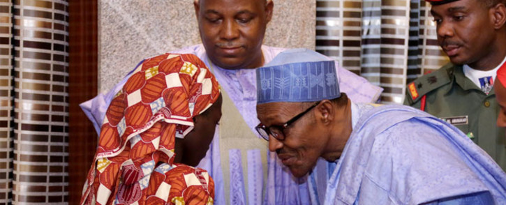 Nigerian President Mohammadu Buhari speaks with Chibok schoolgirl Amina Ali carrying her four-month-old baby as Borno state governor Kashim Shettima (C) looks on at her arrival at the presidency in Abuja, on 19 May 2016. Picture: AFP.