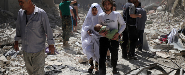 FILE: A Syrian family walks amid the rubble of destroyed buildings following a reported airstrike in Aleppo. Picture: AFP.