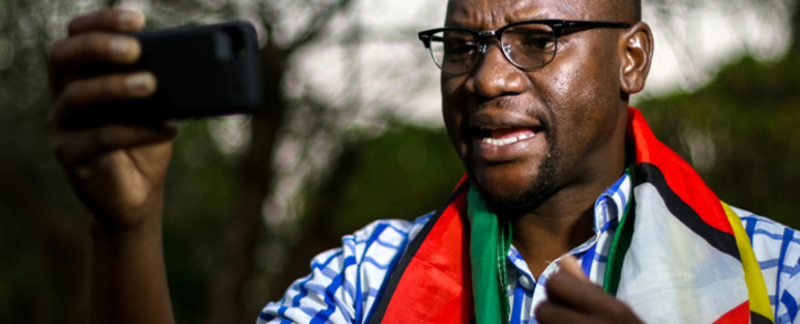 This file photo taken on 19 May 2016 shows Zimbabwean cleric Evan Mawarire, wrapped in the Zimbabwean national flag, recording an installment of his #ThisFlag video series. Picture: AFP.