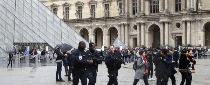 FILE: Police officers patrol in front of the Louvre Pyramid in Paris following an attempted terror attack. Picture: AFP.