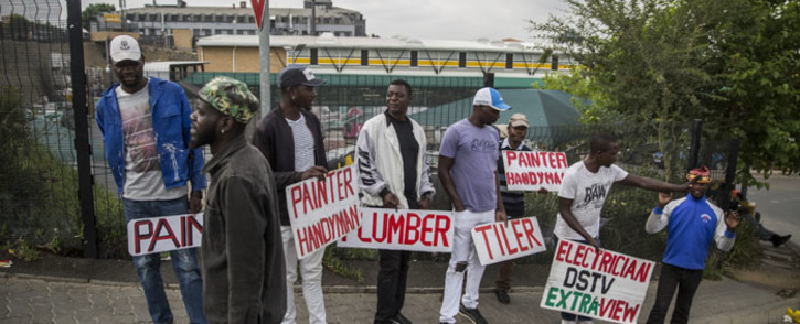 FILE: Unemployed builders, tilers and plumbers hold signs seeking jobs on the side of the road in Johannesburg in November 2019. Picture: AFP