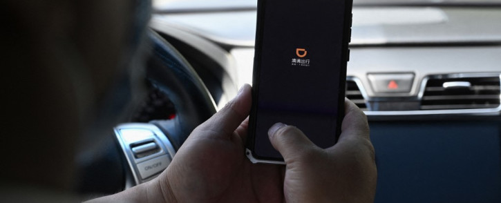 FILE: This file photo taken on 2 July 2021 shows a driver opening the Didi Chuxing ride-hailing app on his smartphone in Beijing. China's new data security law takes effect from 1 September 2021, the latest effort to tighten oversight of the country's mammoth tech sector. Picture: Jade GAO/AFP