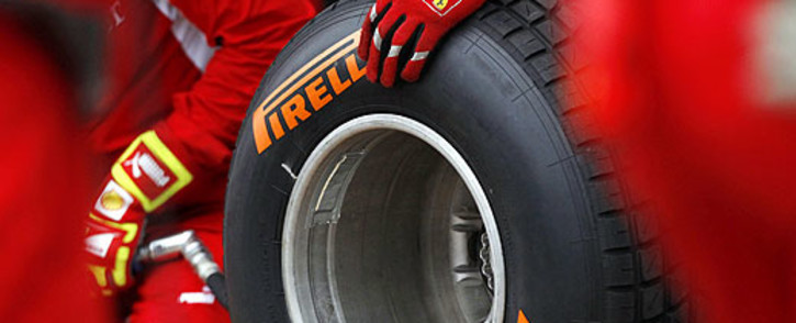 Scuderia Ferrari technicians handle a wet Formula 1 Pirelli tyre at a Grand Prix. Picture: AFP