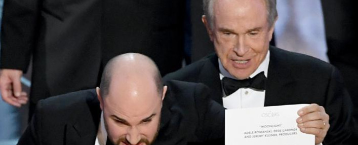 FILE: 'La La Land' producer Jordan Horowitz (L) holds up the winner card reading actual best picture winner 'Moonlight' with actor Warren Beatty onstage during the 89th Annual Academy Awards at Hollywood & Highland Center on 26 February 2017 in Hollywood, California. Picture: AFP.