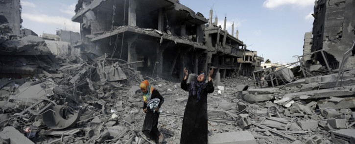 FILE: A Palestinian woman pauses amid destroyed buildings in the northern district of Beit Hanun in the Gaza Strip during a humanitarian truce on 26 July, 2014. Picture: AFP.