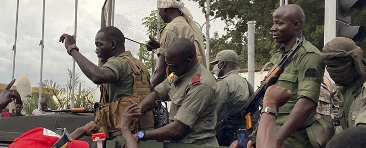 Hundreds of anti-government protesters poured into a central square in Bamako to celebrate and cheer the mutineers as they drove through in military vehicles and fired rounds of celebratory gunfire. Picture: AFP