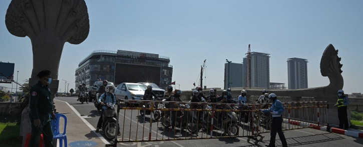 Police stand guard as they lock down a bridge to Koh Pich (Diamond Island), as motorists wait behind a barrier, in Phnom Penh on February 20, 2021, after authorities found 32 local cases of Covid-19 coronavirus. Picture: Tang Chhin Sothy / AFP.