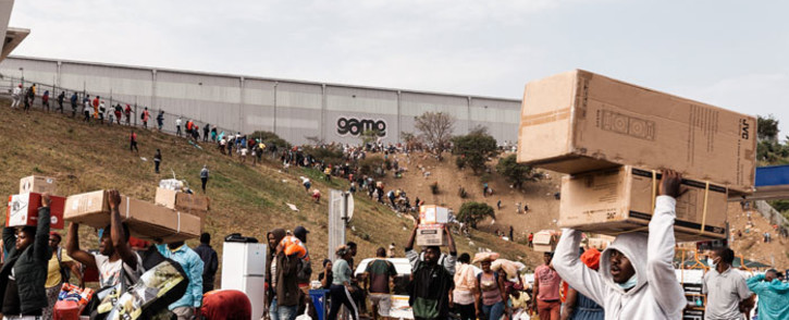Suspected looters carry goods from the Game Warehouse in Durban on 13 July 2021. Picture: AFP