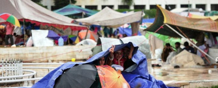 Pakistani supporters of Canadian cleric Tahir ul Qadri take cover under plastic sheeting during heavy rain on the lawn of the Parliament premises during an anti-government protest in Islamabad on 4 September 2014. Picture: AFP.