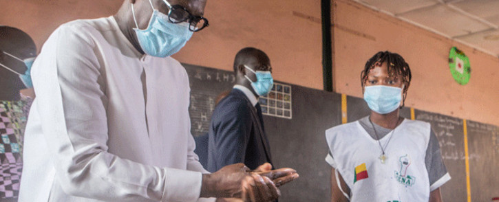 Benin President Patrice Talon sanitises his hands as he arrives to cast his ballot at the Charles Guiyot Zongo public school on May 17, 2020 as voting operation are under way for the local election. Picture: Yanick Folly / AFP.